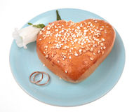 Marriage proposal. Wedding rings, cake and a flower ona  blue plate Royalty Free Stock Photography