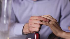 Marriage proposal. Closeup man wearing ring on woman`s hand. Marriage proposal. Closeup man wearing engagement ring on woman`s hand in restaurant stock video