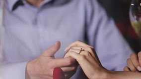 Marriage proposal. Closeup man wearing ring on woman`s hand. Marriage proposal. Closeup man wearing engagement ring on woman`s hand in restaurant stock video footage