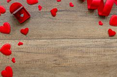 Marriage proposal and engagement concept with romantic arrangement felt red hearts, and ring box on wooden background stock photos