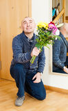 Marriage proposal. Guilty man asks forgiveness with bouquet of flowers stock images