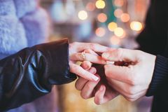 The marriage proposal. Romantic wedding proposal where guy wear a ring on a girl`s finger during the Christmas time royalty free stock images