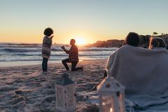 Marriage proposal at sunset beach. Man proposing woman her loved at sea shore. Marriage proposal at sunset beach with friends sitting in front wrapped in a stock images