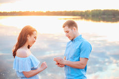 Marriage proposal on sunset . young man makes a proposal of betrothal to his girlfriend on the beach stock photography