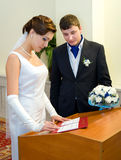Marriage registration. A bride signs at the marriage registration, her bridegroom is beside Stock Photo