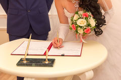 Marriage. Registration of marriage, the bride with a bouquet of flowers signed a marriage contract with a ballpoint pen, selective focus Stock Photo