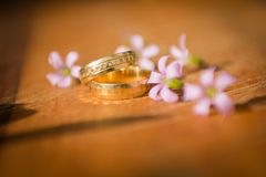 Marriage ring walpaper. Wedding ring in the sunlight, with some flowers composing. Image related to marriage that ends up generating the union of a new couple royalty free stock photo