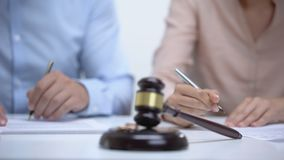 Marriage rings and gavel closeup, spouses signing divorce document on background. Stock footage stock video