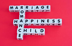 Marriage and romance. Text ' happiness, marriage, child, romance ' inscribed in black uppercase letters on small white cubes arranged crossword style, red Stock Photo