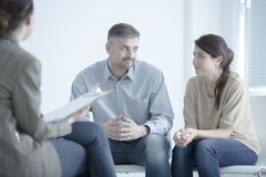 Marriage trying to reconcile. While talking to each other during marriage therapy with mediator Stock Images
