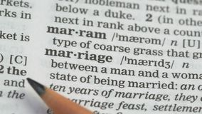 Marriage, word pointed in dictionary, agreement between couple, love and family. Stock footage stock video