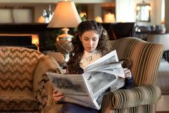 Marriageable girl is sitting in an old-fashioned armchair, dressed in a vintage velvet purple dress and reading a newspaper stock image