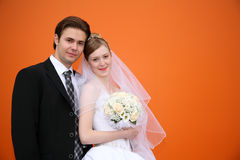 Married against orange bck Royalty Free Stock Photos