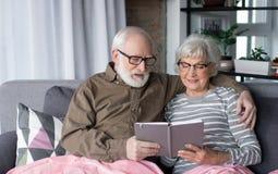 Married alterte die Paare, die Fotoalbum untersuchen lizenzfreie stockfotografie