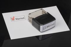 Married - checkbox with a cross on white paper with handle Rubber Stamper. Checklist concept stock photo