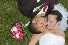 Married couple. Just married multi ethnic couple laying in the grass Stock Photo
