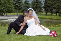 Married couple. Just married multi ethnic couple sitting in the grass stock image