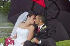 Married couple. Just married multi ethnic couple kissing under an umbrella Royalty Free Stock Image