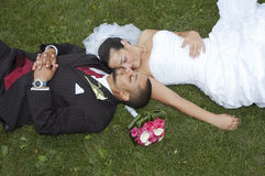 Married couple. Just married multi ethnic couple laying in the grass stock photography