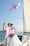Married couple. Vertical photo  newly married couple stand on  white yacht, outdoor Stock Image