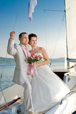 Married couple. Vertical photo  newly married couple stand on  white yacht, outdoor Royalty Free Stock Image