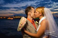 Married couple. Just married couple kissing near the river at sunset time Royalty Free Stock Image