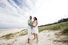 Married couple. A married caucasian couple standing bare feet in the sand dunes on the beach stock photo