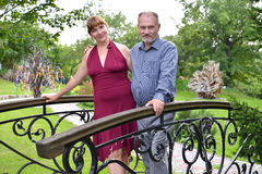 The married couple of average years is installed on the decorative bridge in the park Stock Photo