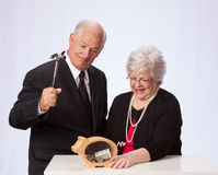 Married Couple Breaking the Piggy Bank for Retirement Royalty Free Stock Image