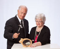 Married Couple Breaking the Piggybank for Retirement. Retirement aged married couple are about to break the piggy bank to count their money in United States Stock Image