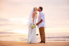 Married couple, bride and groom, kissing at sunset on beautiful Royalty Free Stock Images