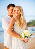 Married couple, bride and groom at sunset on beautiful tropical Stock Photography