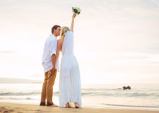 Married couple, bride and groom at sunset on beautiful tropical Royalty Free Stock Image