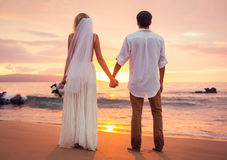 Married couple, bride and groom at sunset on beautiful tropical Royalty Free Stock Photo