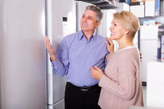 Married couple chooses refrigerator in shop Royalty Free Stock Photo