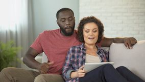 Married couple choosing furniture for new apartment, using mobile shopping app