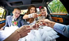 married couple clinking glasses with friends in car Stock Photo