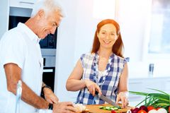 Married couple cooking at home. Happy mature couple cooking together at home Royalty Free Stock Photo