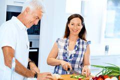 Married couple cooking at home. Happy mature couple cooking together at home Stock Photo