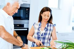 Married couple cooking at home. Happy mature couple cooking together at home royalty free stock image