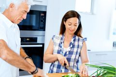 Married couple cooking at home. Happy mature couple cooking together at home royalty free stock photography