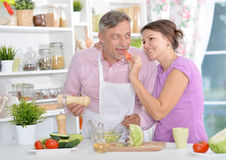 Married couple cooking together. Happy married couple cooking together on kitchen Royalty Free Stock Images