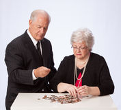 Married Couple Counts Coins for Retirement. Retirement aged married couple are counting their coins on white background. The husband and wife are concerned about Royalty Free Stock Images