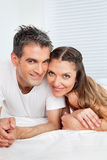 Married couple cuddling in bed Stock Images