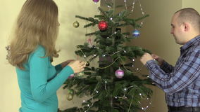 Married couple decorate fir tree with ball toys on Christmas eve stock footage