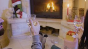 Married couple drinks wine and relaxing near fireplace. Happy married couple sits on the floor near the fireplace and drinks wine. Husband and wife have a good stock footage