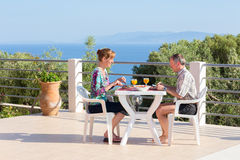 Married couple eating at table on terrace near sea stock photo