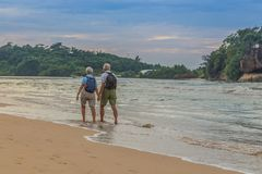 Married couple of elderly people on the beach on the ocean shore.  Stock Photo
