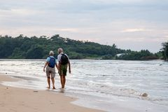 Married couple of elderly people on the beach on the ocean shore.  Stock Photos
