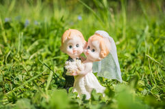 Married couple figurine of bride and groom on grass Stock Photos